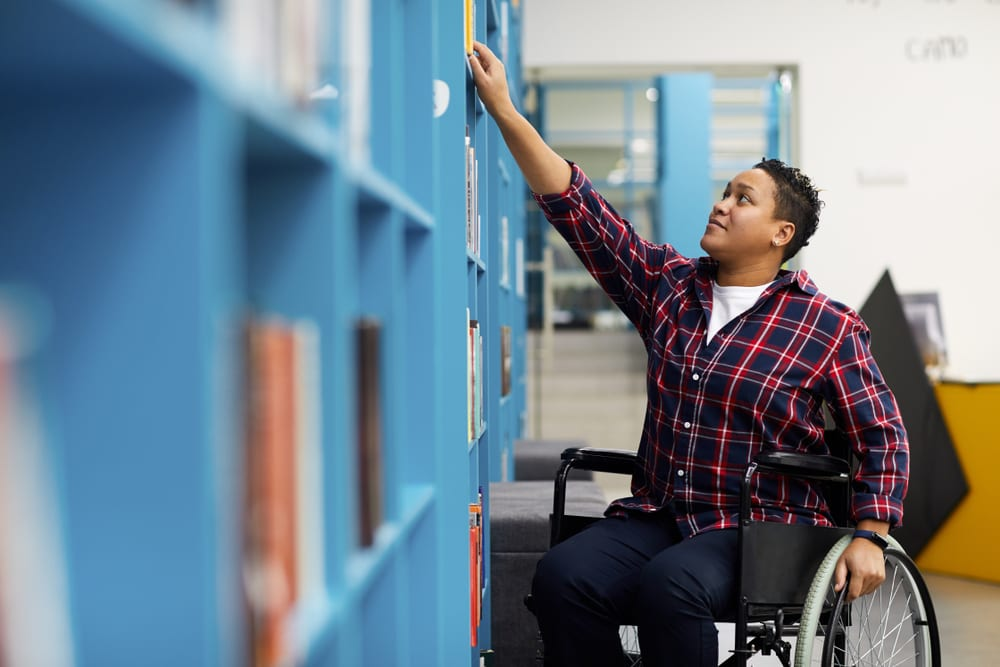 Portrait of disabled student in wheelchair choosing books while studying in college library